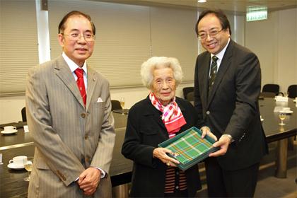 Professor Tsui presenting the gift of a Tartan stole to Mr Tse's mother, Mrs Tse Wong Mee-Kuen