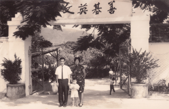 Ms Cynthia Lau and her parents at the entrance Shan Ji, the boarding school that her parents established.