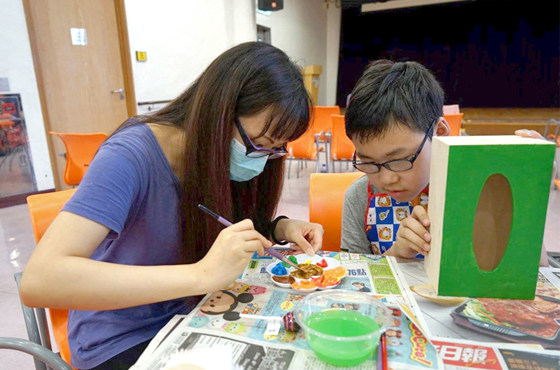 Linda helping a visually impaired boy to finish his piece at a workshop organised by The Jockey Club Scholars Alumni Association.